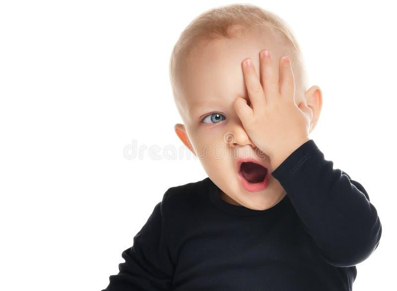 Ritratto del ragazzo di sbadiglio divertente che si siede sul pavimento isolato su bianco immagini stock