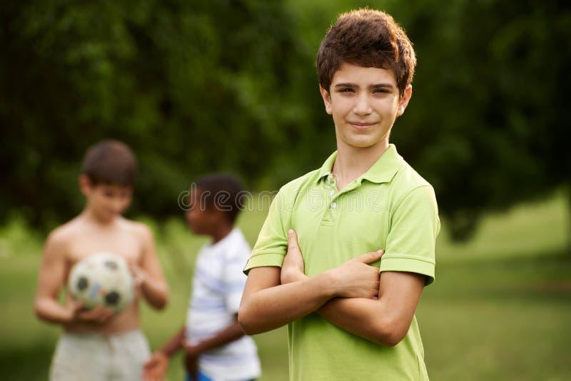 Ritratto del ragazzo e degli amici che giocano a calcio nel parco immagini stock