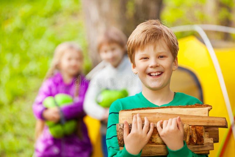 Ritratto del ragazzo felice che tiene il legno per il falò fotografia stock libera da diritti
