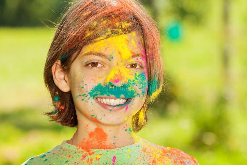 Ritratto del ragazzo felice spalmato di polvere colorata immagine stock libera da diritti