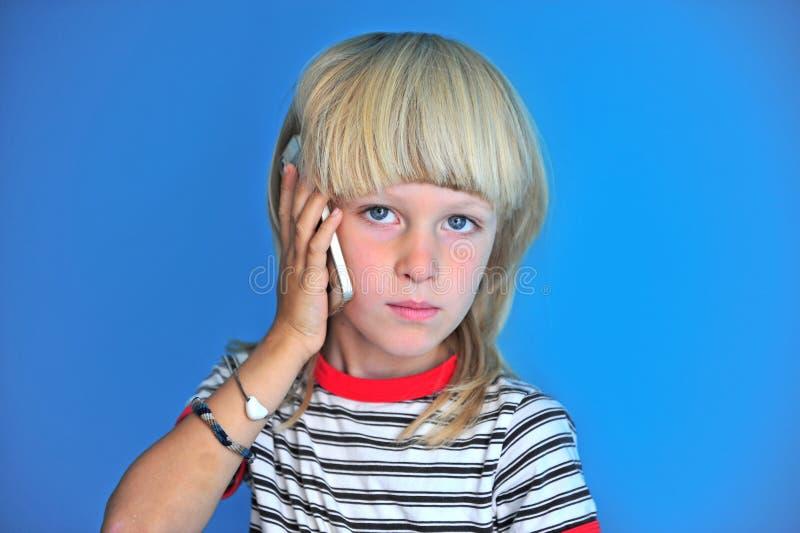 Ritratto del ragazzo lungo biondo dei capelli che parla dal telefono cellulare fotografia stock libera da diritti