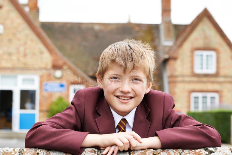 Ritratto del ragazzo nell'edificio scolastico esterno uniforme fotografia stock