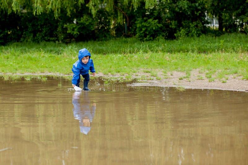Ritratto del ragazzo sveglio del bambino che gioca con la nave fatta a mano ragazzo di asilo che naviga un crogiolo di giocattolo fotografia stock libera da diritti