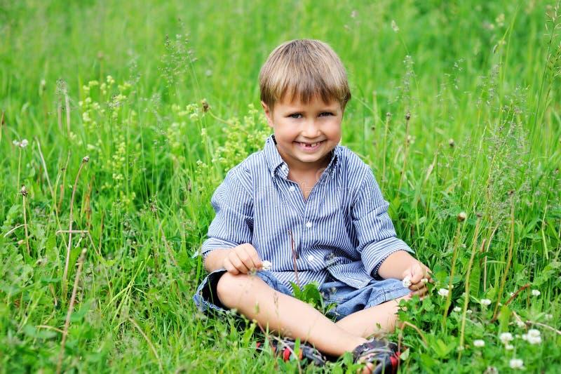 Ritratto del ragazzo sveglio che si siede sull'erba verde immagine stock libera da diritti