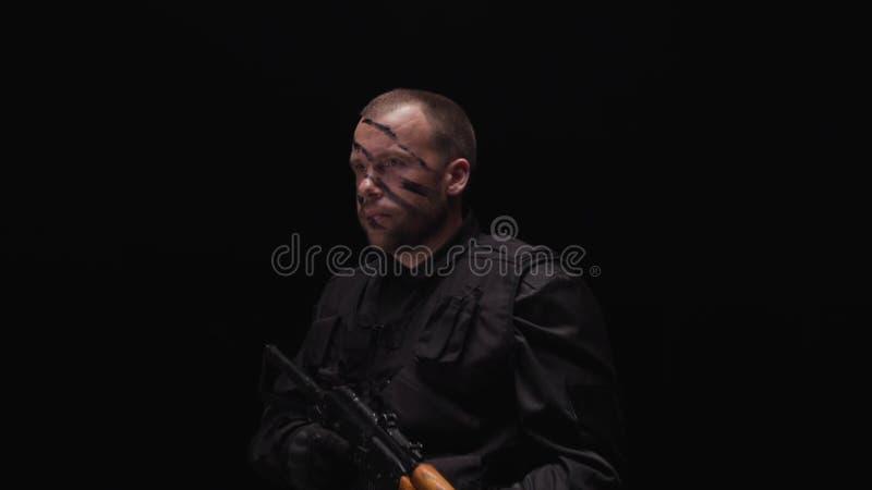 Ritratto del soldato bello che porta un'uniforme militare, dipinto il suo fronte su fondo nero azione Militare con i pollici in s fotografia stock libera da diritti