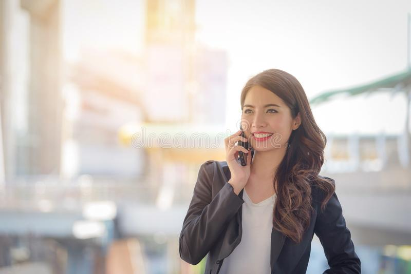 Ritratto del sorriso felice della donna di affari che parla sullo spirito dello smartphone fotografia stock