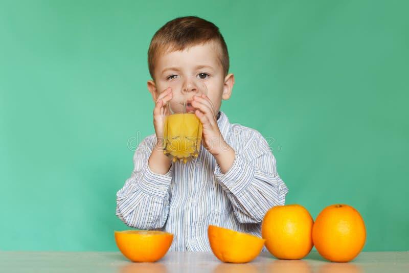 Ritratto del succo d'arancia bevente del ragazzino felice fotografie stock