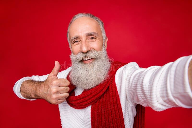 Ritratto del suo bel contenuto allegro e allegro nonnino con i capelli grigi, che dà una pubblicità a pollici immagini stock