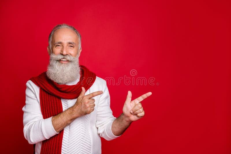 Ritratto del suo bel contenuto allegro un uomo dai capelli grigi che punta due dita di fronte da parte e decisione pubblicitaria immagini stock