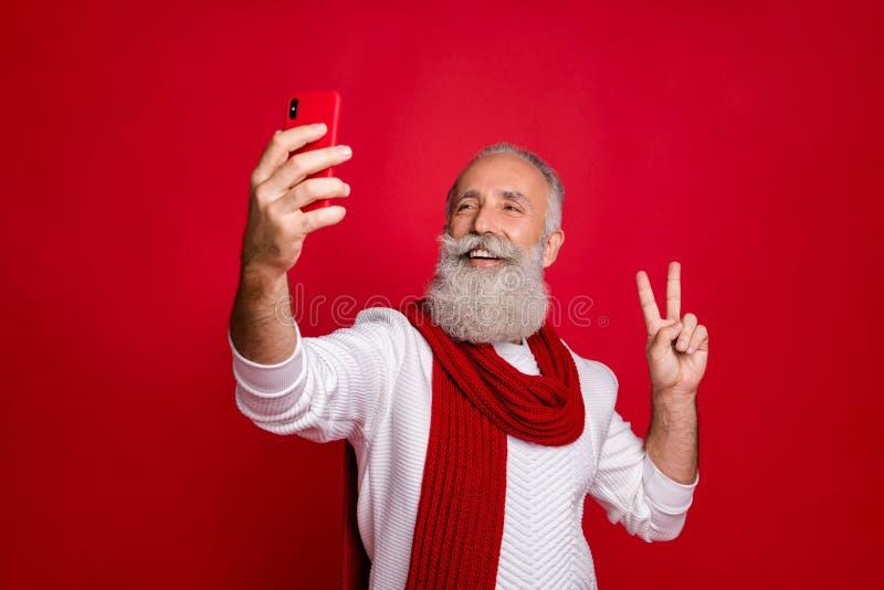 Ritratto del suo simpatico allegro allegro allegro allegro e felice uomo dai capelli grigi che si fa il selfie che mostra il simb immagini stock