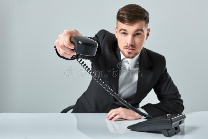 Ritratto del telefono attraente della tenuta dell'uomo d'affari in sua mano Questa chiamata è per voi concetto immagini stock libere da diritti
