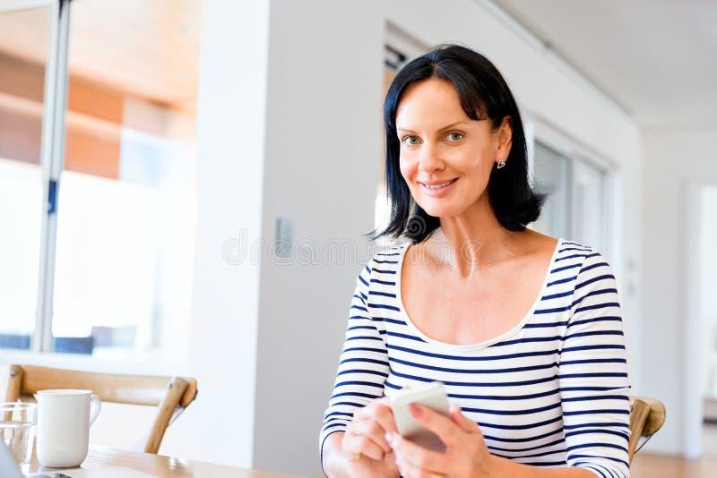 Ritratto del telefono attraente della tenuta della donna fotografia stock