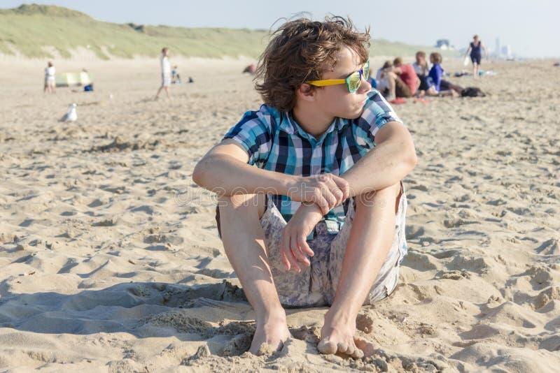 Ritratto del tipo adolescente che si siede sulla sabbia fotografia stock