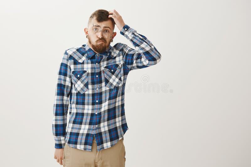 Ritratto del tipo esile bello divertente con la barba, attrezzatura e vetri d'avanguardia d'uso, graffiare capo e sporgere le lab immagini stock