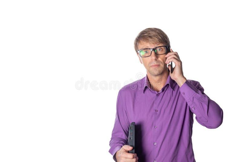 Ritratto del tipo invecchiato medio che tiene un computer portatile e che parla sul telefono cellulare sopra fondo bianco immagini stock