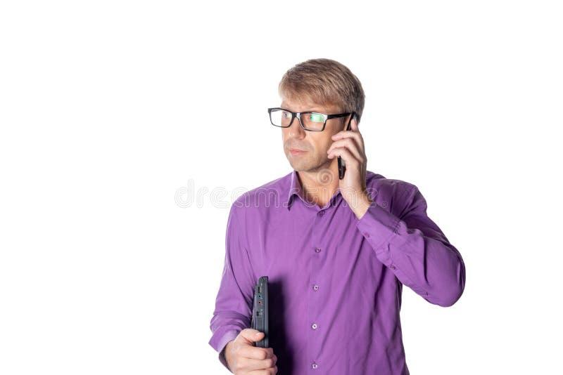 Ritratto del tipo invecchiato medio che tiene un computer portatile e che parla sul telefono cellulare sopra fondo bianco fotografie stock