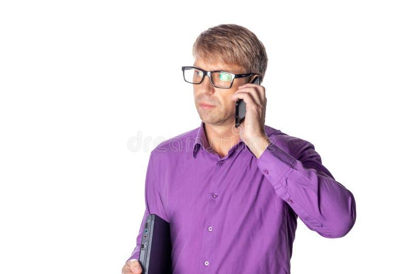 Ritratto del tipo invecchiato medio che tiene un computer portatile e che parla sul telefono cellulare sopra fondo bianco fotografia stock