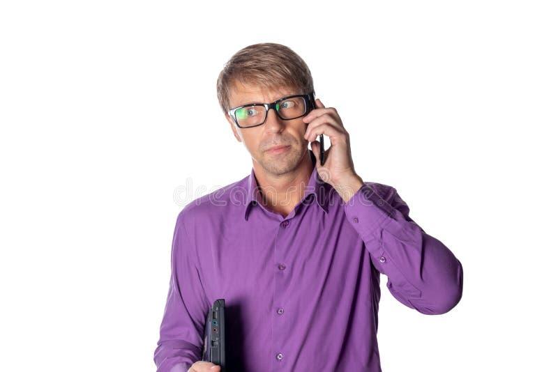 Ritratto del tipo invecchiato medio che tiene un computer portatile e che parla sul telefono cellulare sopra fondo bianco immagini stock libere da diritti