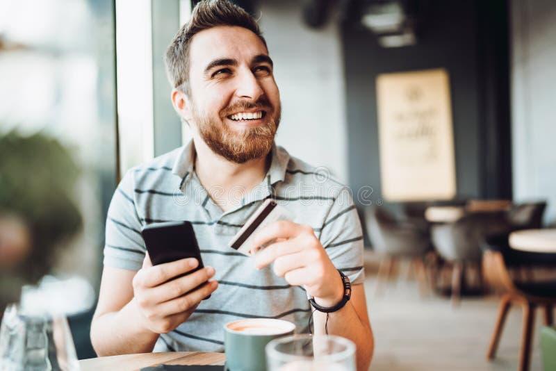 Ritratto del tipo sorridente che effettua pagamento online con lo smartphone Acquisto dell'uomo sul telefono cellulare e pagare d fotografie stock libere da diritti