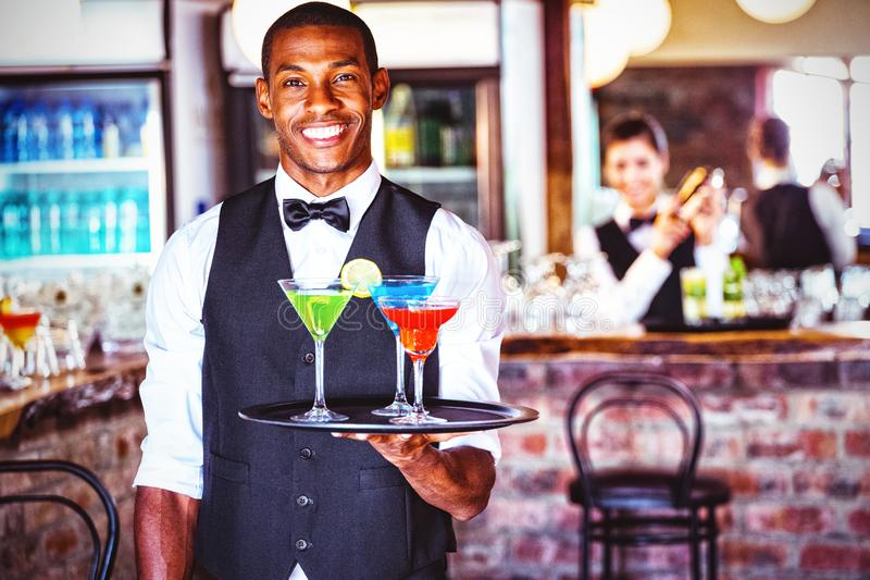 Ritratto del vassoio del servizio della tenuta del barista con i vetri di cocktail fotografia stock libera da diritti