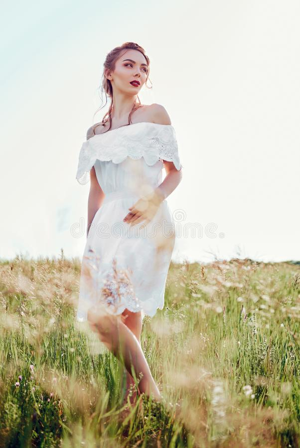 Ritratto del vestito bianco d'uso dalla bella giovane donna nel campo immagine stock libera da diritti