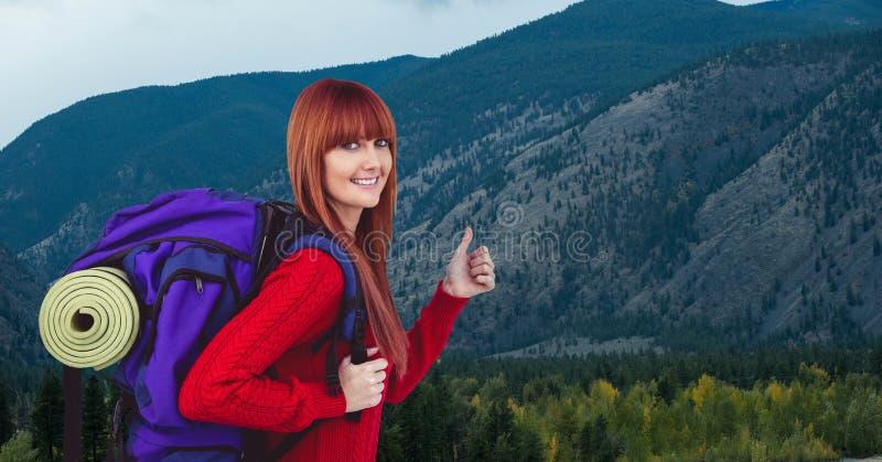 Ritratto del viaggiatore femminile felice che mostra i pollici su contro la montagna fotografie stock