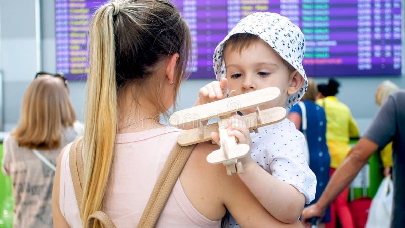 Ritratto del volo aspettante dell'aeroplano del piccolo ragazzo del bambino e della giovane madre in terminale di aeroporto immagini stock