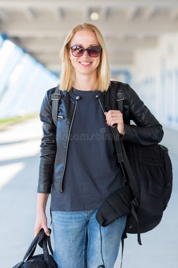 Ritratto dell'abbigliamento casual d'uso del giovane viaggiatore femminile allegro che porta zaino e bagagli pesanti all'aeroport fotografie stock libere da diritti