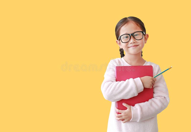 Ritratto dell'abbraccio d'uso sorridente del monocolo della scolara asiatica un libro e giudicare una matita a disposizione isola immagine stock