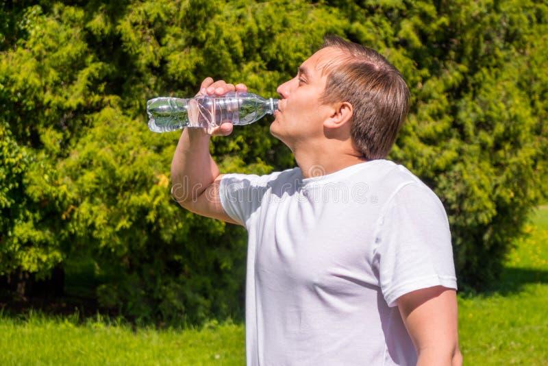 Ritratto dell'acqua potabile degli uomini da una bottiglia, nella condizione bianca della maglietta esterna in parco immagini stock libere da diritti