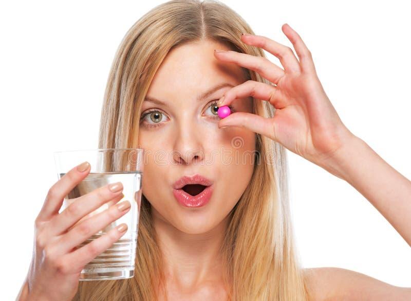Ritratto dell'adolescente con la tazza di acqua che mostra pillola fotografie stock libere da diritti