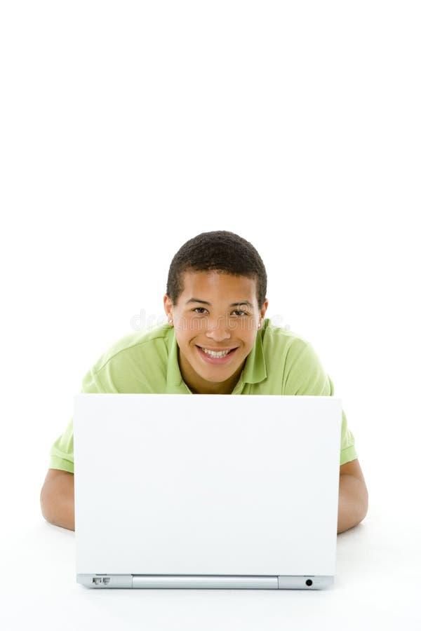 Ritratto dell'adolescente sul suo computer portatile immagine stock libera da diritti