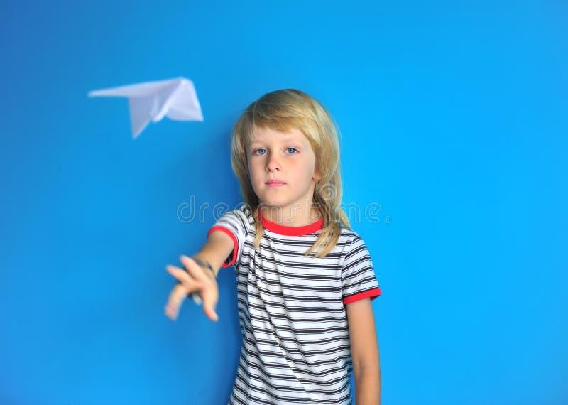 Ritratto dell'aereo di carta di lancio del ragazzo sveglio lungo dei capelli immagine stock