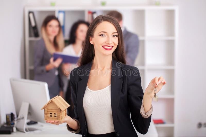 Ritratto dell'agente immobiliare con la famiglia che ottiene nuova casa Affare fotografie stock