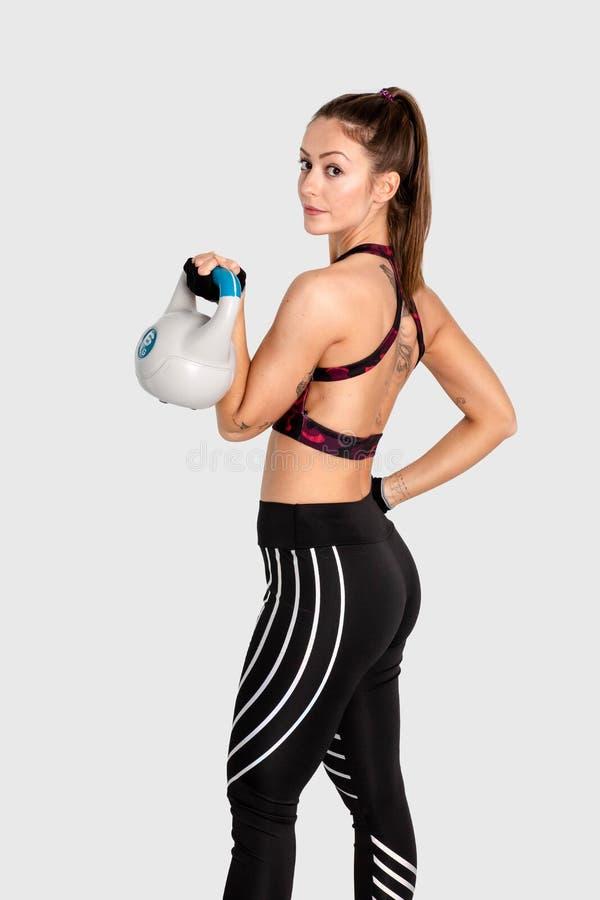 Ritratto dell'allenamento muscolare di esercizio della giovane donna, sport di formazione con i kettlebells, culturismo sano di f fotografia stock