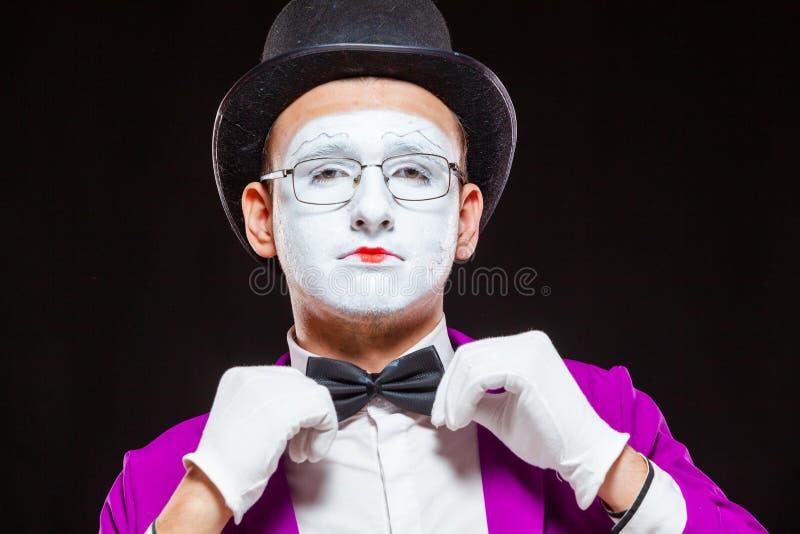 Ritratto dell'artista mime maschio, isolato sullo sfondo nero Vicino alla faccia dell'uomo L'uomo regola il suo arco fotografia stock