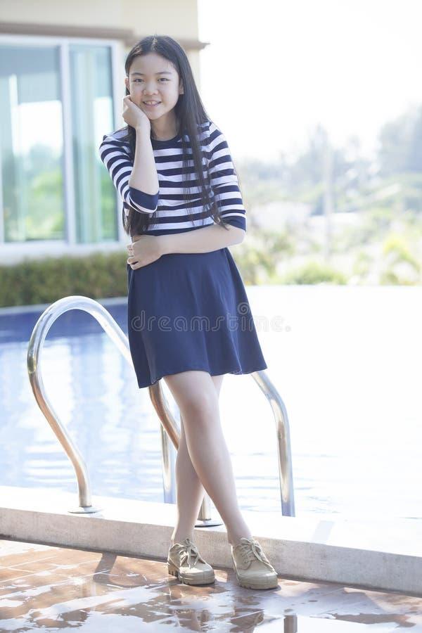 Ritratto dell'età teenager asiatica che sta accanto alla relaxina della piscina fotografia stock