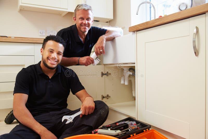 Ritratto dell'idraulico con l'apprendista in cucina domestica immagini stock