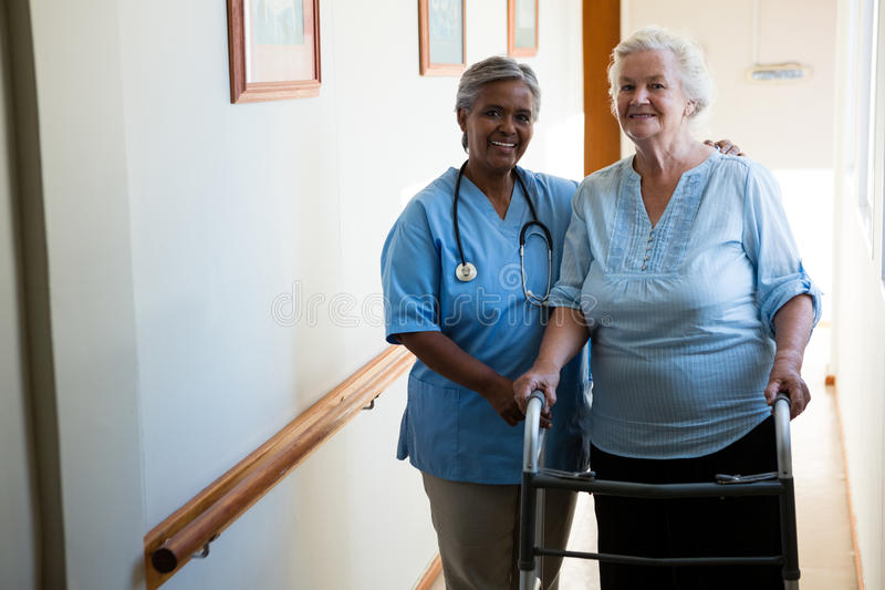 Ritratto dell'infermiere che assiste paziente senior nella camminata con il camminatore fotografia stock