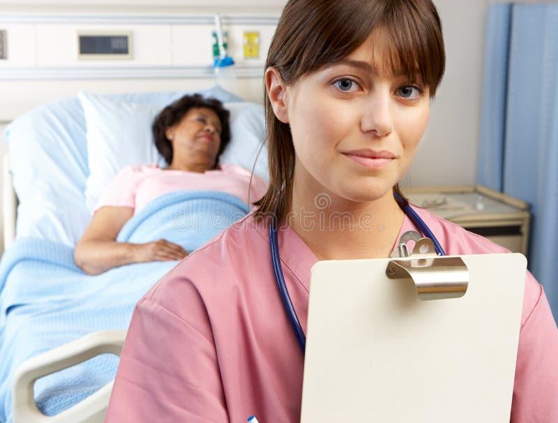 Ritratto dell'infermiere con il paziente nel fondo immagine stock