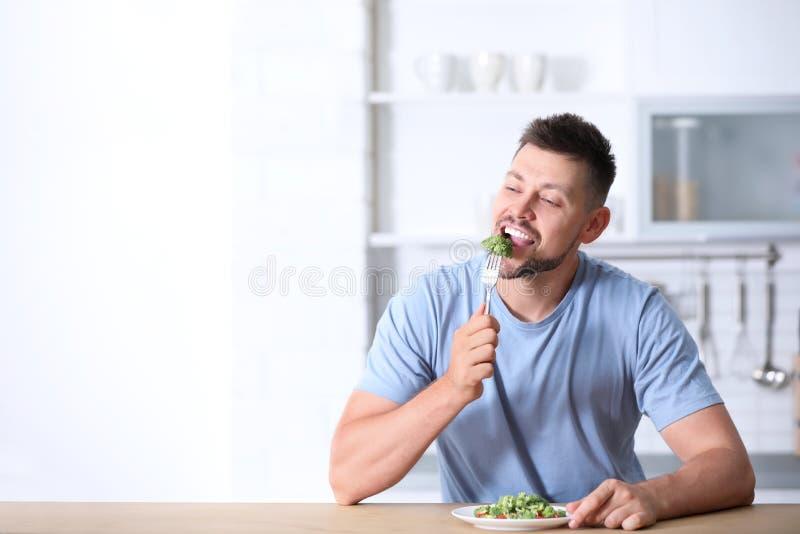Ritratto dell'insalata mangiatrice di uomini felice dei broccoli fotografie stock libere da diritti