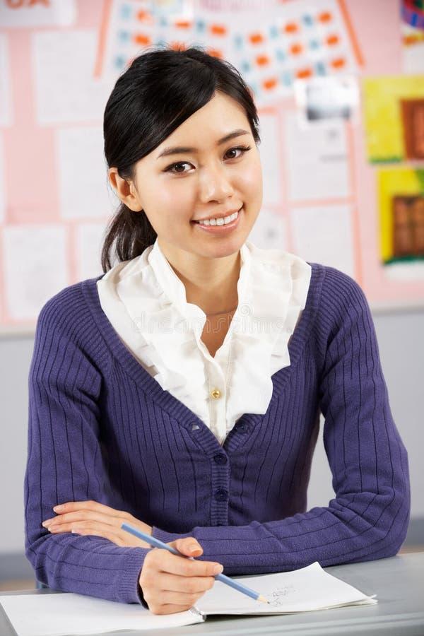 Ritratto dell'insegnante cinese che si siede allo scrittorio immagine stock