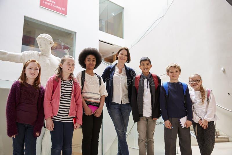 Ritratto dell'insegnante With Class Standing dentro il museo fotografia stock libera da diritti