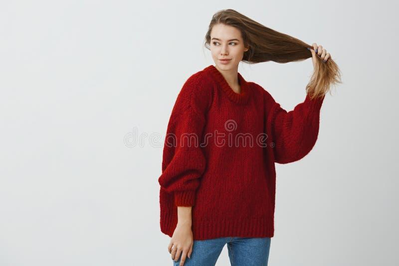 Ritratto dell'interno della donna caucasica romantica curiosa in maglione rosso sciolto, giudicante bei capelli sani disponibili  immagini stock libere da diritti