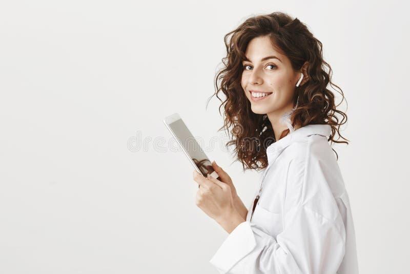Ritratto dell'interno della donna caucasica sveglia affascinante con il sorriso tenero che sta nel profilo con la compressa in ma immagini stock