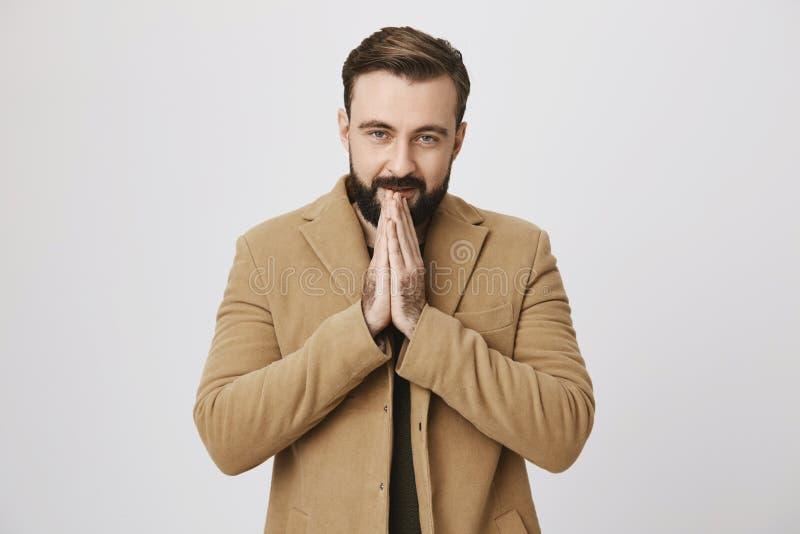 Ritratto dell'interno della vita-su del modello europeo barbuto attraente in cappotto, mani di riscaldamento con respiro caldo, f immagine stock