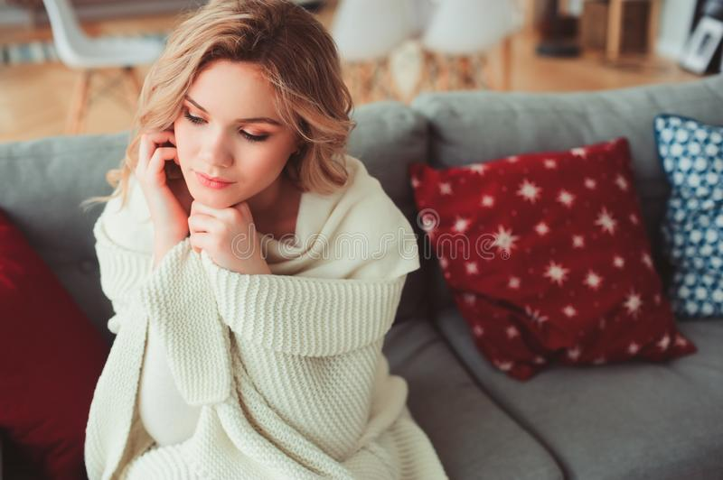 Ritratto dell'interno di giovane bella donna egoista che gode dell'orario invernale a casa, sedentesi sullo strato accogliente in fotografia stock