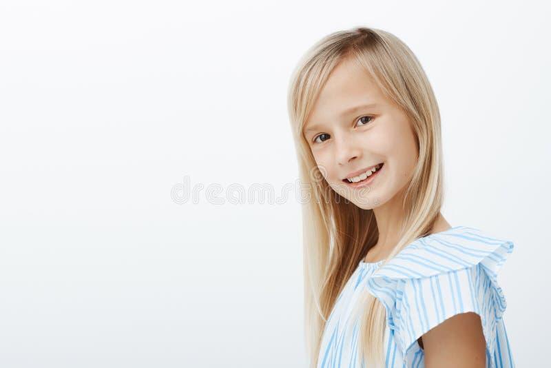 Ritratto dell'interno di profilo di incantare ragazza bionda caucasica in blusa blu d'avanguardia, di sorridere largamente e di r fotografia stock
