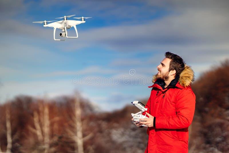 Ritratto dell'operatore del fuco che pilota gli aerei del uav, quadcopter Dettagli di tecnologia con il fuco ed il telecomando fotografia stock libera da diritti