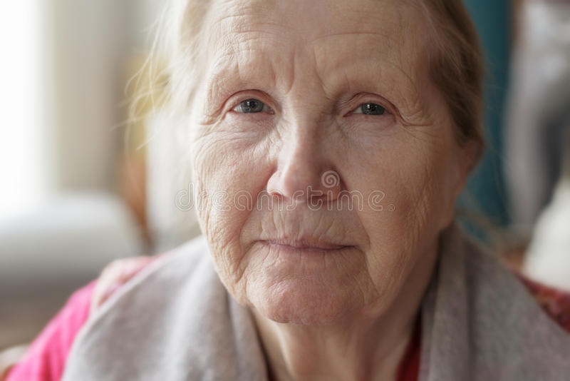 Ritratto dell'ubicazione senior della donna vicino alla finestra fotografia stock libera da diritti